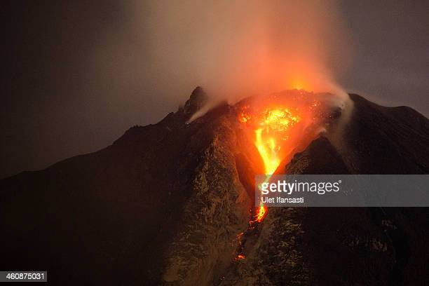 Hot lava runs down Mount Sinabung from a lava dome on January 5 2014 in Karo District North Sumatra Indonesia The number of displaced persons has...