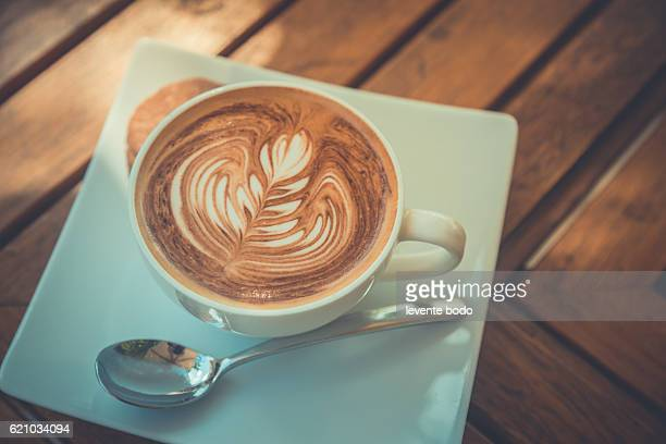 Hot milk art coffee on wooden table. Summer relaxing mood