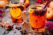 Hot mulled apple cider with cinnamon sticks, cloves and anise on wooden background