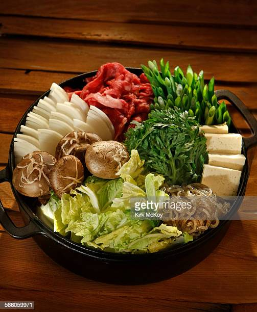 with onions shataki mushrooms cabbage noodles tofu green onions and beef in the sukiyaki