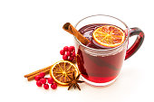 Hot red mulled wine isolated on white background with christmas spices, orange slice, anise and cinnamon sticks.