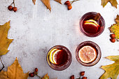 Hot red tea with lemon on light gray table with copy space viewed from above, delicious autumn mulled wine drink