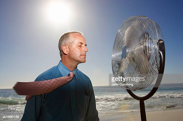 Hot, Relieved Businessman With His Eyes Closed Standing Next to an Electric Fan on a Beach