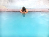 Woman soaking in hot turquoise colored water. Geothermal travertine pool near the San Juan River, Colorado.