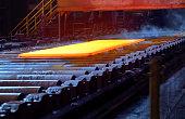 Hot steel plate on conveyor inside of steel plant