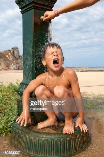 Hot summer. Child drinking and taking a shower. : Stock Photo