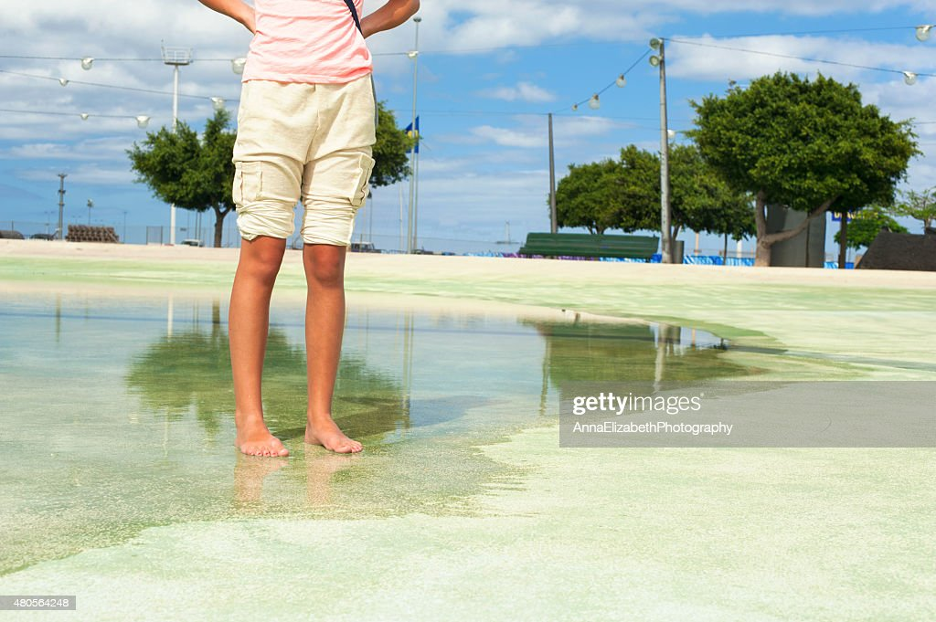 Hot summer in the city. Legs and feet in water : Stock Photo