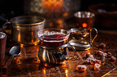 Hot tea with candle in cold winter evening