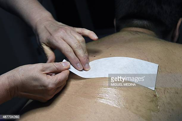 Hot wax is smeared on the back of a man as he has the hair on his back removed at a beauty salon in Paris on September 4 2015 AFP PHOTO/MIGUEL MEDINA