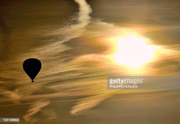 A hotair balloon flies over the city of Godewaersvelde northern France as the sun rises on September 30 2012 AFP PHOTO / PHILIPPE HUGUEN