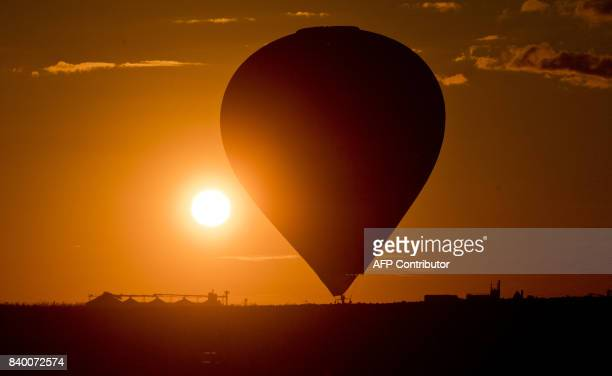 A hotair balloon lands at sunset on a field near Algermissen central Germany on August 27 2017 / AFP PHOTO / dpa / Julian Stratenschulte / Germany OUT