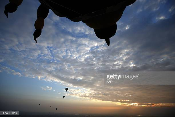 Hotair balloons fly over Joure northern Netherlands on July 24 2013 during the Frisian Balloon Festival Tens of balloon of all kinds from several...