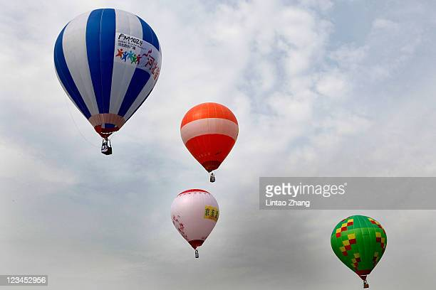 Hotair balloons fly over the city during the Fifth China International Hot Air Balloon Festival on September 3 2011 in Langfang China The festival...