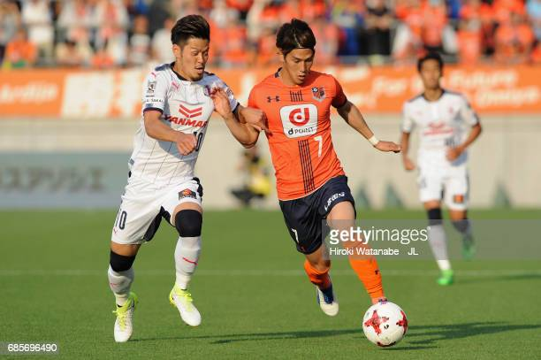 Hotaru Yamaguchi of Cerezo Osaka and Ataru Esaka of Omiya Ardija compete for the ball during the JLeague J1 match between Omiya Arija and Cerezo...