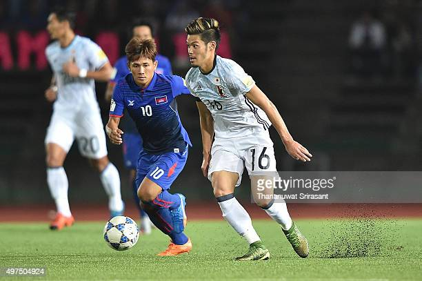 Hotaru Yamaguchi of Japan and Keo Sokpheng of Cambodia compete for the ball during the 2018 FIFA World Cup Qualifier match between Cambodia and Japan...