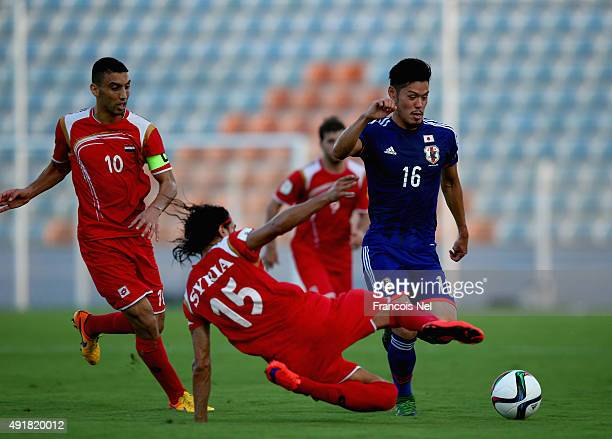 Hotaru Yamaguchi of Japan compete for the ball with Alaa Al Shbbli of Syria during the 2018 FIFA World Cup Asian Group E qualifying match between...