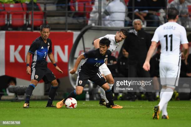 Hotaru Yamaguchi of Japan controls the ball under pressure of Kosta Barbarouses of New Zealand during the international friendly match between Japan...