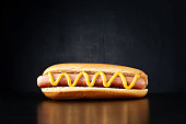 Hotdog with big sausage and mustard isolated on black background. Front view.