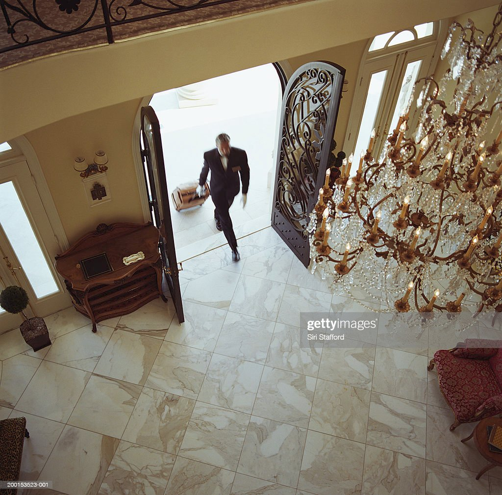 Hotel attendant carrying luggage inside, elevated view