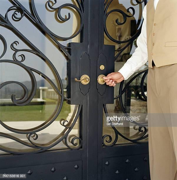 Hotel attendant opening door (mid section)