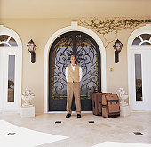 Hotel attendant standing by doorway with luggage, portrait