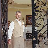 Hotel attendant standing in doorway, portrait