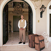 Hotel attendant standing in doorway with luggage, portrait