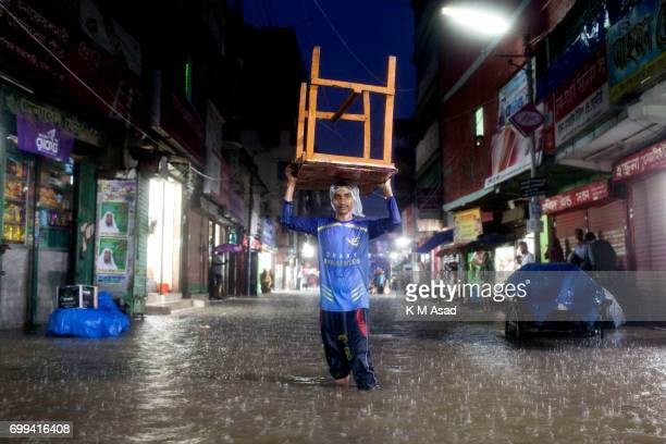 OLD DHAKA DHAKA BANGLADESH A hotel boy transfer table when heavy rainfall made waterlogging in Dhaka city The death toll rises to 150 in several hill...