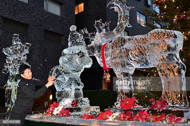 Hotel chef and world ice carving champion Yoshihito Kosaka shaves ice to make a 18metre Santa Claus and reindeer at a hotel in Tokyo on December 24...