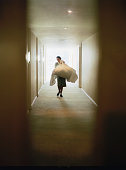 Hotel cleaning staff carrying laundry in hallway