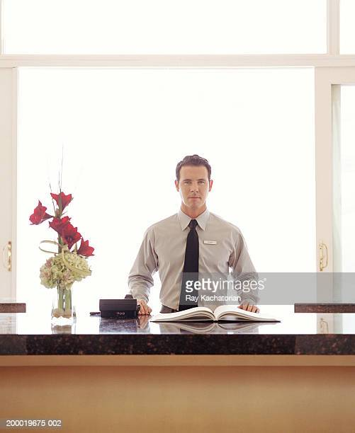 Hotel clerk at front desk, guest book on counter