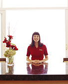Hotel clerk at front desk, smiling