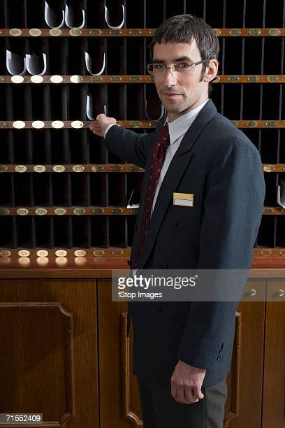 Hotel clerk reaching for paper in pigeon hole