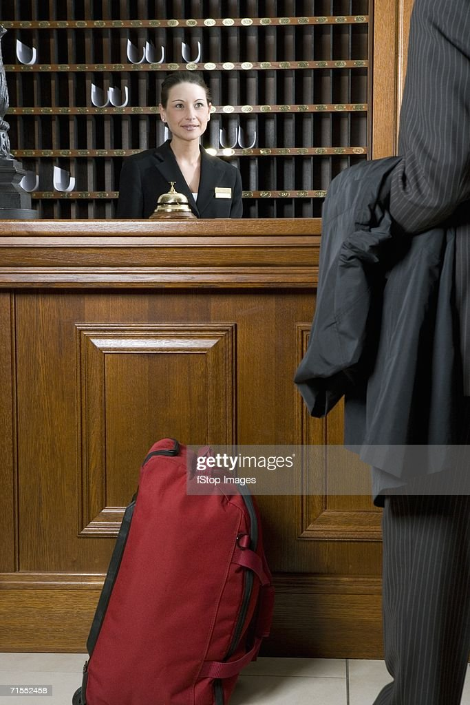 Hotel clerk serving businessman at hotel reception : Stock Photo