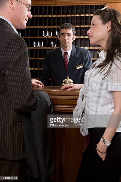 Hotel clerk serving young woman and mature man at hotel reception