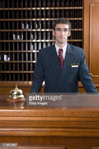Hotel clerk standing behind desk in hotel reception
