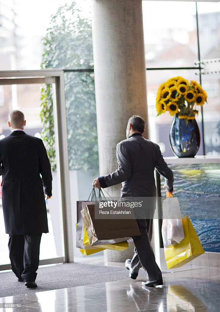 Hotel concierge takes out shopping bags : Stock Photo
