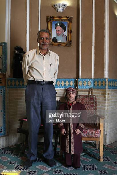 Hotel doorman Aboul Fazl Kalantari and driver Mohammad Ali Khabiri pose for a portrait in front of the Ayatollah Khomeini while awaiting guests at...