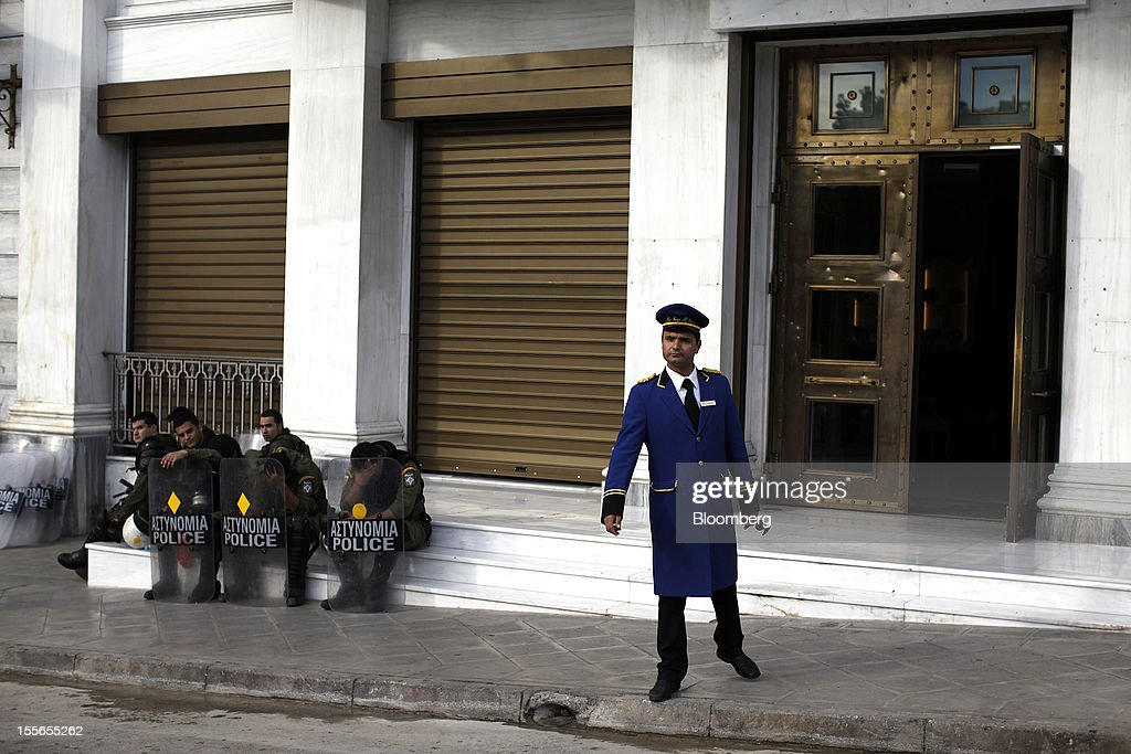 A hotel doorman checks the street in front of a hotel as riot police sit and wait during a general strike protest in Athens, Greece, on Tuesday, Nov. 6, 2012. Greece headed for a cliffhanger vote on austerity measures needed to keep the bailout on track as a 48-hour general strike began and European officials squabbled over the timing of a deal to unlock rescue funds. Photographer: Kostas Tsironis/Bloomberg via Getty Images