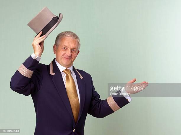 Hotel doorman lifting top hat
