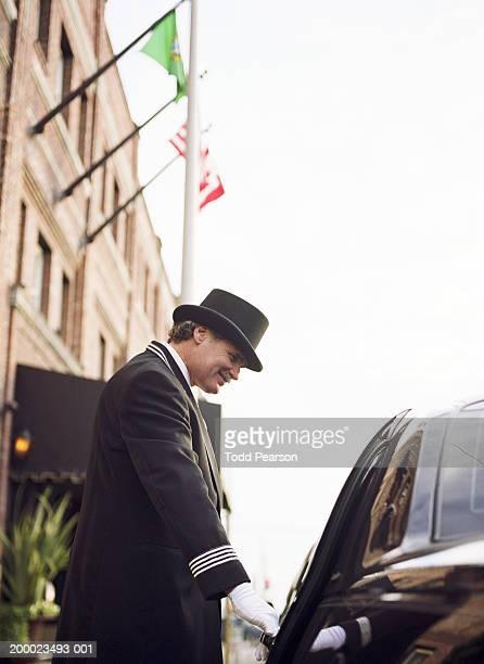 Hotel doorman opening car door, low angle view