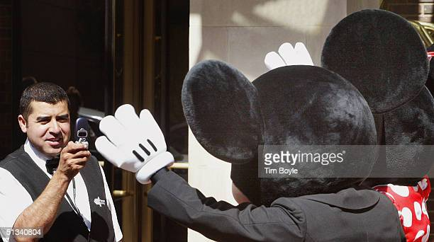 A hotel doorman uses his camera phone to photograph Mickey and Minnie Mouse near the Disney Store September 23 2004 in Chicago Later outside the...