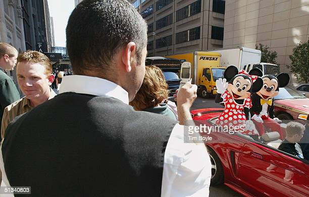 A hotel doorman uses his camera phone to photograph Minnie and Mickey Mouse near the Disney Store September 23 2004 in Chicago Later outside the...