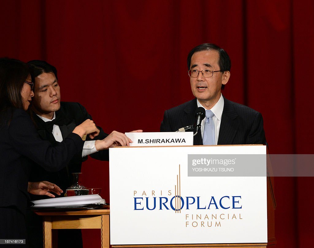 A hotel employee puts a name card for Bank of Japan Governor Masaaki Shirakawa as he deliveres a speech at the luncheon of the Paris Europlace financial forum in Tokyo on December 3, 2012. Shirakawa and his French counterpart Christian Noyer attended the meeting. AFP PHOTO / Yoshikazu TSUNO