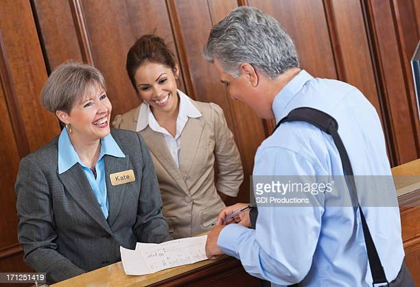 Hotel front desk workers discussing stay and bill with guest
