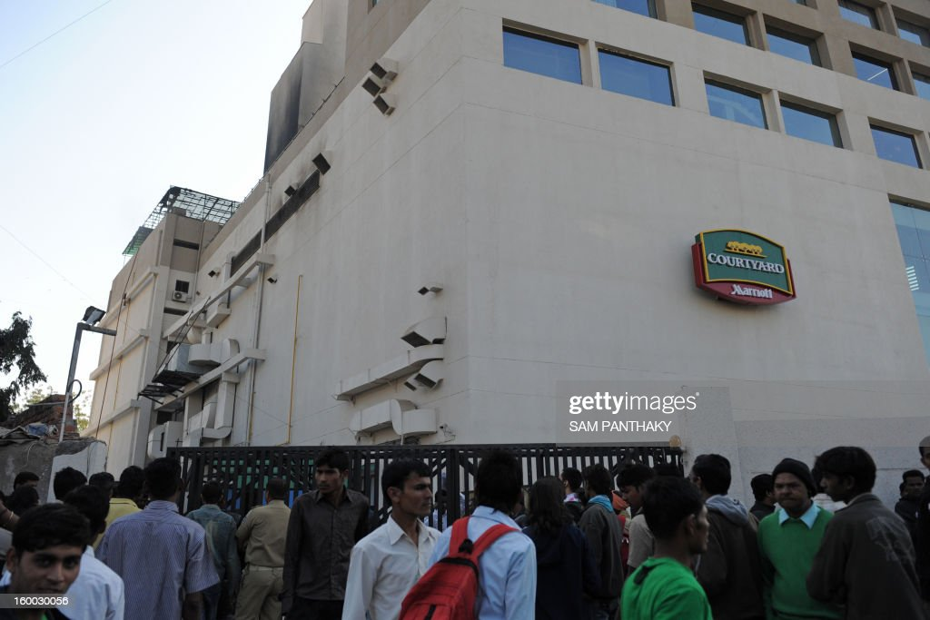 Hotel guests and onlookers stand outside the Courtyard Marriott Hotel following a fire in a kitchen duct on the premises in Ahmedabad on January 25, 2013. No casualties have been reported thus far. The hotel had experienced a previous fire incident in March 2011. AFP PHOTO / Sam PANTHAKY