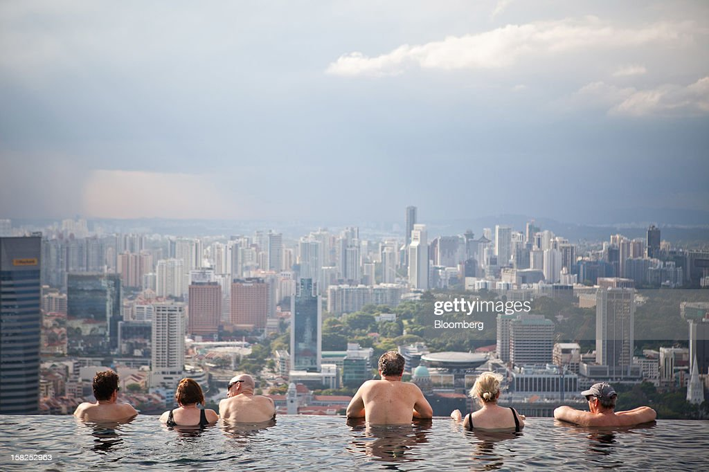 'BEST PHOTOS OF 2012' (): Hotel guests in the infinity pool at the SkyPark atop Marina Bay Sands look out towards the city skyline in Singapore, on Tuesday, Feb. 28, 2012. The number of visitors to the island rose to a record 13.2 million in 2011 as casino-resorts run by Genting Singapore Plc and Las Vegas Sands Corp. lured tourists. Photographer: Sam Kang Li/Bloomberg via Getty Images