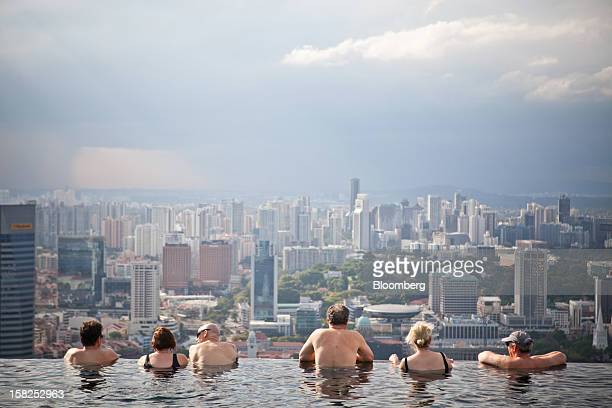 'BEST PHOTOS OF 2012' Hotel guests in the infinity pool at the SkyPark atop Marina Bay Sands look out towards the city skyline in Singapore on...