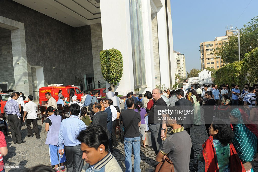 Hotel guests stand outside the Courtyard Marriott Hotel following a fire in a kitchen duct on the premises in Ahmedabad on January 25, 2013. No casualties have been reported thus far. The hotel had experienced a previous fire incident in March 2011. AFP PHOTO / Sam PANTHAKY
