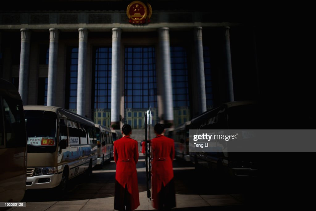 Hotel guide for delegates waits outside the Great Hall of the People during a presidium meeting after a pre-opening session of the National People's Congress, China's parliament, on March 4, 2013 in Beijing, China. China's defensive military policies have played a core role in maintaining peace and stability in Asia, a spokesperson for the annual session of China's national legislature said Monday.